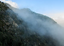 The fog goes up covering the mountains.  royalty free stock images