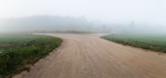 Fog and gravel road. Gravel road in the fog. Rural landscape. Panorama shot Royalty Free Stock Photography