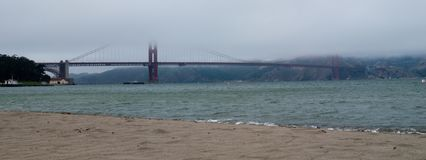 Fog Hanging Over The Golden Gate Bridge. View of The Golden Gate Bridge in fog from Crissy Field stock photo