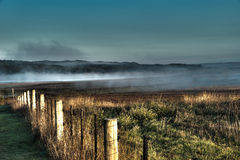 Fog in the hollows. A paddock in the early morning with a dusting of fog Royalty Free Stock Photo