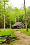 Fog hovers over an old log home in the Smokies. Royalty Free Stock Images