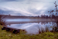 Fog on lake in evening. After rain in autumn. Wet bench on shore of lake Royalty Free Stock Images
