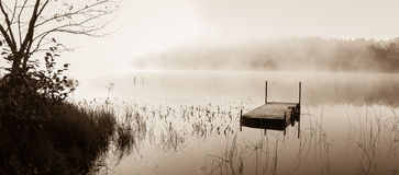 Fog on a still water lake in sepia. Royalty Free Stock Images
