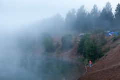 Fog on the lake with standing tourist tents Royalty Free Stock Photography