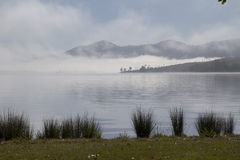 Fog lifting in the early morning on Somerset Dam. Queensland, Australia.  This gives an eerie, creepy feeling in the still morning Royalty Free Stock Image
