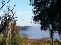 Fog lifts from a lake. Early in the morning the heavy fog rises from a small lake stock photos