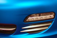 Fog light of german exclusive sport car with blue matte car wrap. Fog light of exclusive sport car covered with blue matte car wrap foil. Car was displayed on stock photo