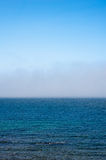 Fog low over wavy water under blue sky Stock Photo