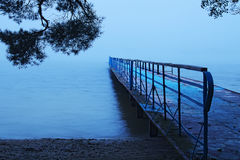 Fog in the morning by the lake. Old metal pier.  stock images