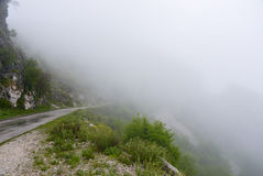 The fog on the mountain pass. The asphalt road along the edge of the slope lost in the fog on the mountainpass at Montenegro Royalty Free Stock Images