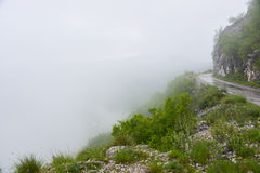 The fog on the mountain pass. The asphalt road along the edge of the slope lost in the fog on the mountainpass at Montenegro Stock Photo