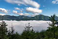 Fog in mountain valley, mountain ridge and blue sky Stock Image
