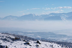 Fog in mountain valley in a sunny winter day Stock Images