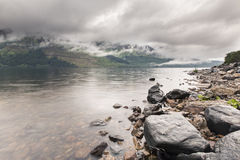 Fog on the mountains and loch in Scotland highlands after the ra Stock Images