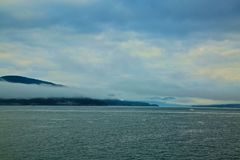Fog mountains ocean. Fog settles in the mountains along the ocean in Royalty Free Stock Photo