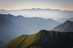 Fog in the mountains, three mountain ranges. With a blue sky on the horizon royalty free stock images