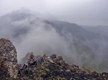 Fog in the mountains, visible stones, a top view of the mountain. The foreground stones dalshe fog, seen dimly adjacent ridges and peaks Stock Image