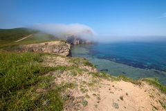 Fog moving to a rock from the sea Royalty Free Stock Photography