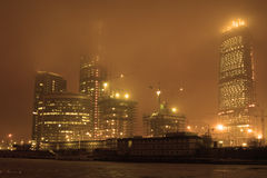 Fog at night city. Highrise buildings under construction, river and fog at night city Royalty Free Stock Image