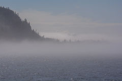Fog on the ocean, the islands are covered in fog. Sea smoke on the bay. Sea smoke is surface fog that appears over the ocean when it is very cold out Stock Photos