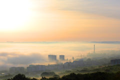 Fog over the city at dawn. Sunrise in foggy morning over the city Stock Images