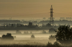 Fog over fields and tower of power lines on the outskirts of the city Royalty Free Stock Image
