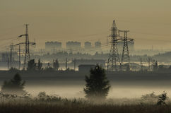 Fog over fields and towers of power lines Royalty Free Stock Photo
