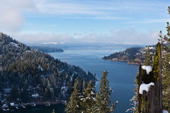 Fog Over Lake Coeur d Alene. Morning fog lifting above the blue water of Lake Coeur d Alene in winter with snow covered trees royalty free stock images