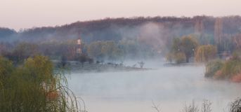 Fog over lake, Corbeanca, Ilfov County, Romania. Fog over lake with woods in early morning in Corbeanca, Ilfov County, Romania Stock Images