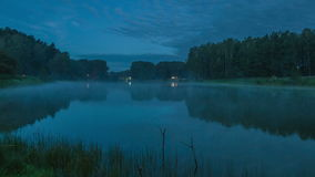 Fog over the lake. Night time. Night time. The lake in the forest. Fog over the water. Picturesque landscape. Wide angle shot. 4k timelapse stock footage
