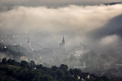 Fog over medieval city of Brasov. Historic medieval city of Brasov, Transylvania, Romania on a foggy morning. Autumn (fall), September 26th, 2016. The steeple Royalty Free Stock Photography