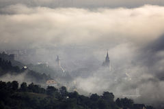 Fog over medieval city of Brasov. Historic medieval city of Brasov, Transylvania, Romania on a foggy morning. Autumn (fall), September 26th, 2016. The steeple Stock Photography