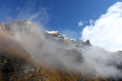 Fog over montain ridge. Rocky mountain ridge with blue sky in the background Royalty Free Stock Images