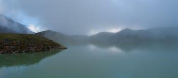 Fog over the mountain lake Stock Photos