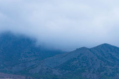 Fog over the mountains. A thick fog over the slopes of the mountains. Gloomy bad weather royalty free stock images