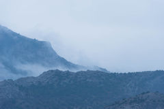 Fog over the mountains. A thick fog over the slopes of the mountains. Gloomy bad weather royalty free stock photo