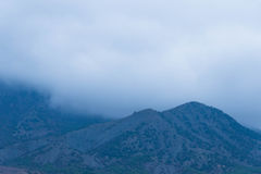 Fog over the mountains. A thick fog over the slopes of the mountains. Gloomy bad weather royalty free stock photography