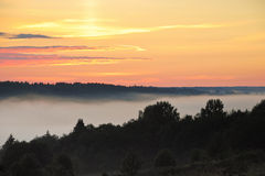 Fog over ravine in forest during summer sunset Royalty Free Stock Photo