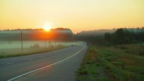 Fog over the road on which cars are passing. Sunrise. Time laps stock footage
