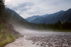 Fog over a rocky mountain stream. Royalty Free Stock Photo