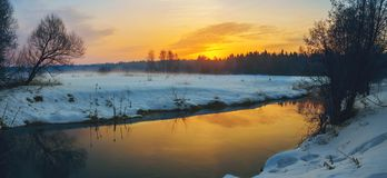 Frosty foggy winter panoramic landscape with small forest river and rising sun. stock photography