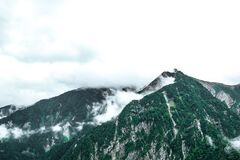 Fog over snowy mountain peaks Stock Image