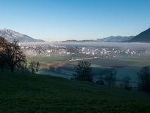 Fog over  a town in the valley. A shot of a town in the valley. The town is covered in fog Stock Photography