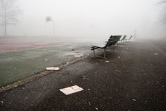 Fog in the park. Park bench in the fog with basketball court on the background Stock Photography