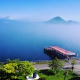Fog and Pier at Lake Toya. Sunshine is dispelling the fog, quiet pier royalty free stock photo