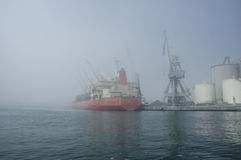 Fog in Port of Malaga. Fog inside Port of Malaga, with a moored ship, tanks and a crane in a pier royalty free stock image