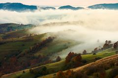 Fog and rising clouds roll over the rural hills. Gorgeous autumn scenery in mountains at dawn stock images