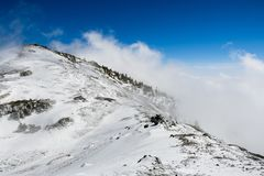 Fog rising from the valley and engulfing a mountain ridge; Mount San Antonio Mt Baldy,south California royalty free stock photography