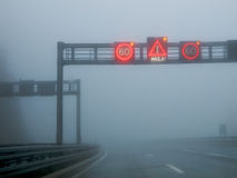 Fog on a road. Notification traffic sign on a highway at strong fog royalty free stock photo
