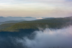 Fog Rolling Through the Catskill Mountains at Dawn. A morning fog tinted with the pink colors of dawn moving through the cloves of the eastern Catskill Mountains stock images